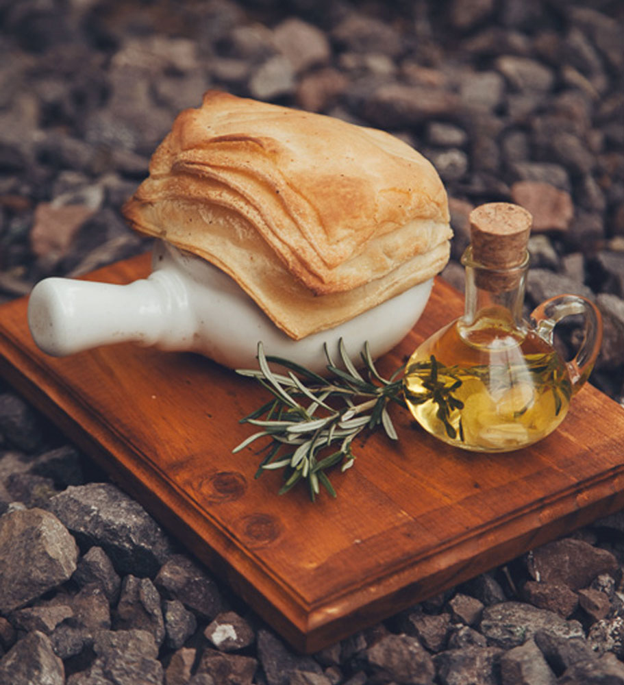Fresh baked bread accompanied by a little bottle of olive oil placed at Green Point Restaurants Garden