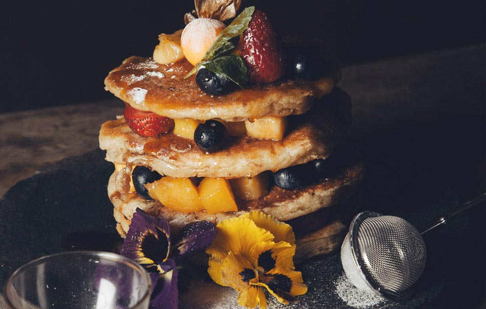 Fluffy vegetarian pancakes made of banana and filled with strawberries, blueberries and papaya.