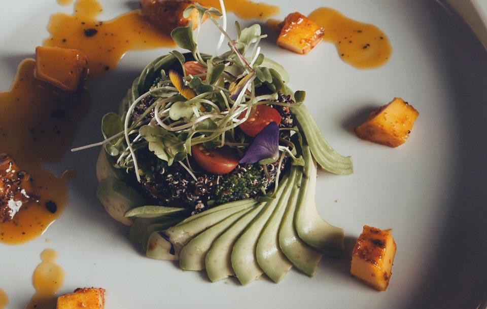Plato Gourmet de ensalada de Quinua decorado con rebanadas de palta y otros vegetales, servido en Green Point Restaurants Cusco.